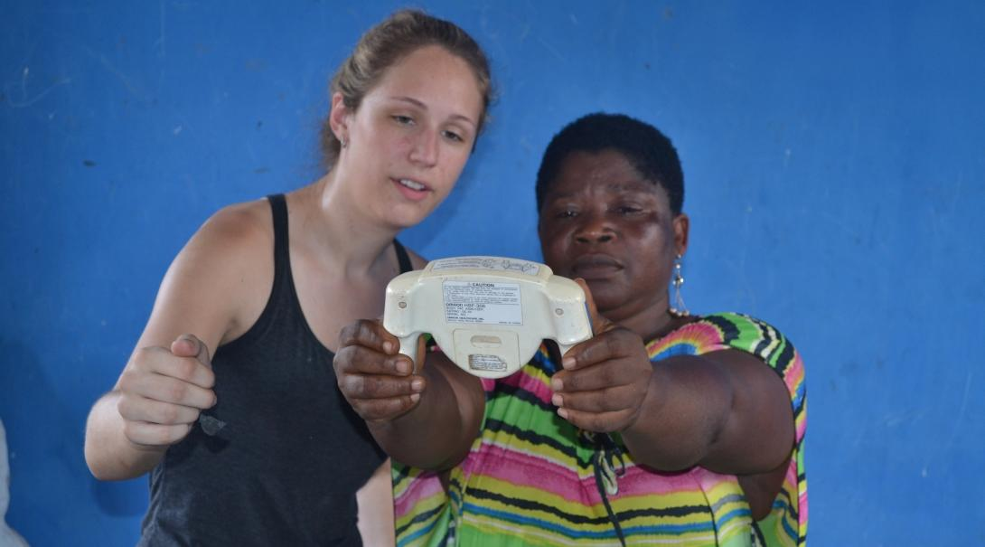 Projects Abroad intern helping a woman at a medical outreach with her treatment during her public health internship in Ghana.